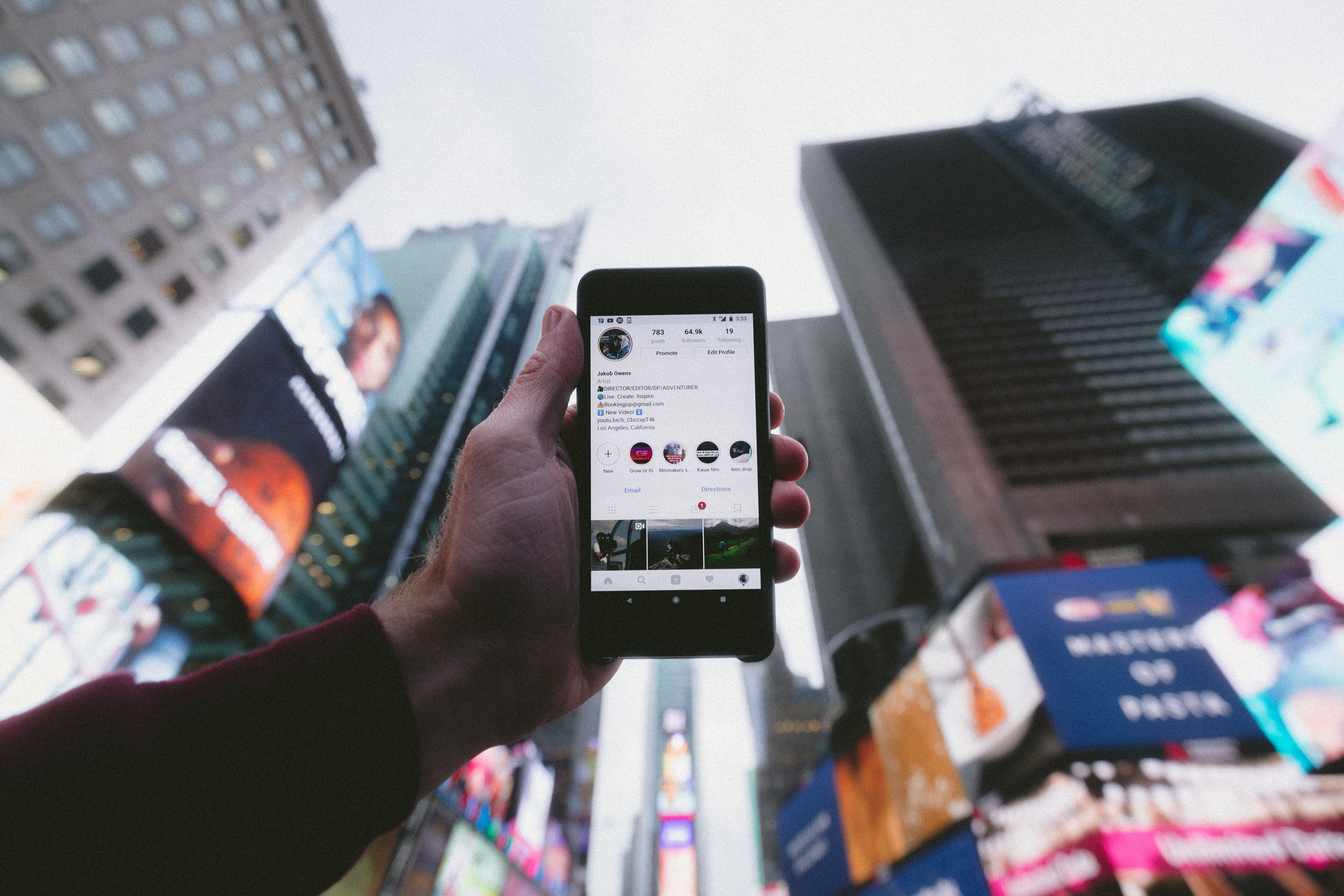 phone with Instagram open held up against skyscrapers in the background